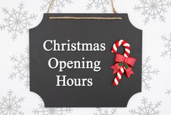 Christmas opening hours message on hanging chalkboard with a candy cane and white and gray snowflakes