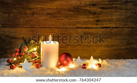 Christmas or Advent candle with red and white christmas ornaments and festive light at snow with wooden background #764304247