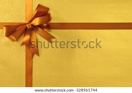 Christmas or birthday gift background gold shiny metallic foil with deep honey gold ribbon and bow