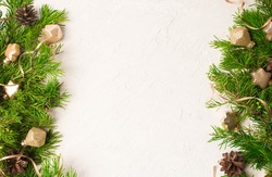 Christmas or New Year background: fir tree branches, gold glass balls, decoration and cones on a white plaster background