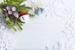 Christmas or New Year background: fur-tree branches, cones, red white jingle bell ball, decoration and glittering on white wood, top view, copy space.