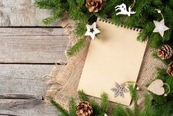 Christmas or new Year background with an open blank Notepad, spruce branches and Christmas ecofriendly wooden decorations. A checklist or a letter to Santa. Copyspace