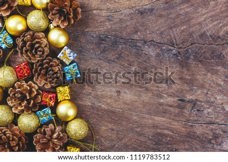 Christmas or New Year background with pine cones,gift box on red ribbon,golden ball of Xmas decorations and fir branches, flat lay, blank space for a greeting text on wooden.  #1119783512