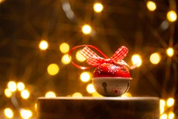 Christmas or New Year card with jingle bell on trendy wooden podium in front of christmas lights in the form of festive bokeh.Close up.