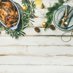 Christmas or New Year celebration table setting. Flat-lay of roast chicken or turkey, plates, silverware and toy holiday decoration over white wooden background, top view, copy space, square crop