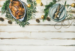 Christmas or New Year celebration table setting. Flat-lay of roast chicken or turkey, plates, silverware and toy holiday decoration over white wooden background, top view, copy space.