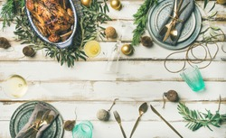 Christmas or New Year celebration table setting. Flat-lay of roast chicken, plates, silverware and toy holiday decoration over white wooden background, top view, copy space