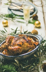 Christmas or New Year celebration table setting. Roast chicken, plates, silverware, glass and toy holiday decoration over rustic white wooden background, selective focus