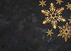 Christmas or New Year dark wooden background, Xmas black board framed with season decorations, space for a text. Christmas Background - Gold Snowflakes On dark background. Golden snowflakes.
