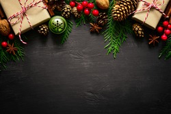 Christmas or New Year dark wooden background, Xmas black board framed with season decorations, space for a text, view from above