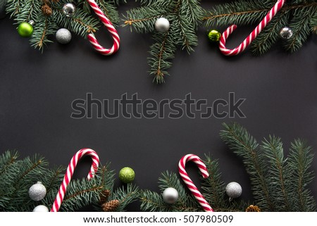 Christmas or New Year decoration background: fir-tree branches, colorful balls, candy on black background with copy space. Top view.
