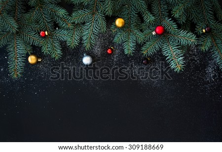 Christmas or New Year decoration background: fur-tree branches, colorful glass balls  on black grunge background with copy space #309188669
