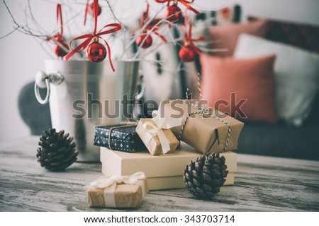 Christmas or new year decoration on modern wooden coffee table. Cozy sofa with pillows on a background. Living room interior and holiday home decor concept. Toned picture