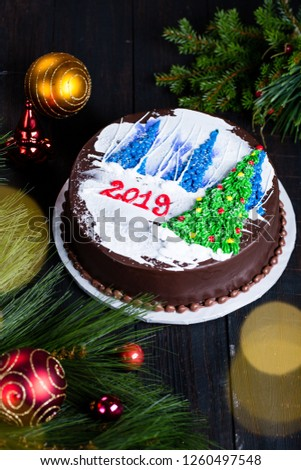 Christmas or New Year eve cake with 2019 words for midnight family celebration dinner dessert table in Christmas arrangement decoration, green fir branches with colorful baubles on dark wooden table #1260497548