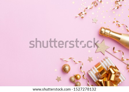 Christmas or New year festive background. Champagne bottle, gift or present box and golden confetti on pink top view. Flat lay.