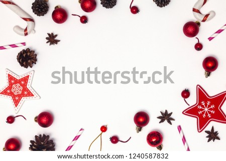 Christmas or new year frame composition. Christmas decorations in red colors on white background with empty copy space for text. Holiday and celebration concept for postcard or invitation. Top view #1240587832