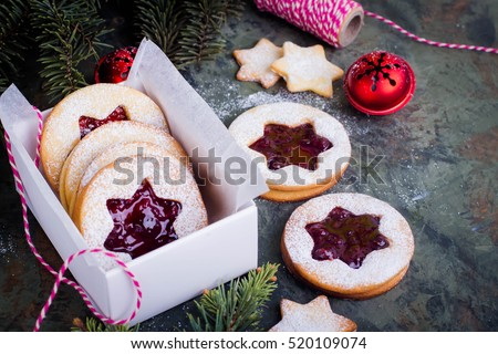 Christmas or New Year homemade sweet present in white box. Traditional Austrian christmas cookies - Linzer biscuits filled with red raspberry jam. Festive decoration. Copy space