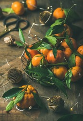 Christmas or New Year table. Fresh ripe tangerines with leaves in tray, decoration toys, scissors and light garland over rustic wooden table background, selective focus, close-up