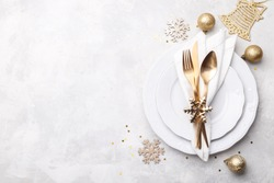 Christmas or new year table setting with golden cutlery on white stone table, card or menu template copy space flat lay