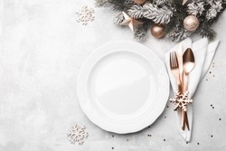 Christmas or new year table setting with rose gold cutlery on white stone table, card or menu template copy space flat lay
