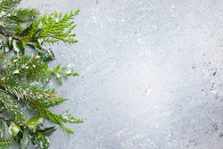 Christmas or winter background with a border of green and frosted evergreen branches on a grey vintage board