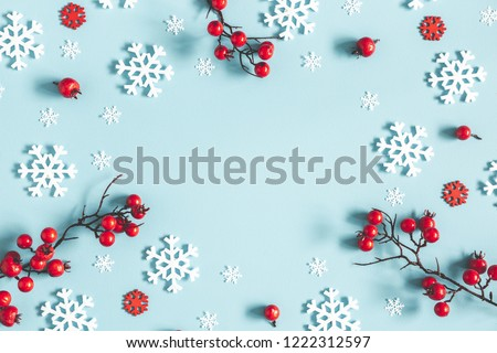 Christmas or winter composition. Frame made of snowflakes and red berries on pastel blue background. Christmas, winter, new year concept. Flat lay, top view, copy space #1222312597