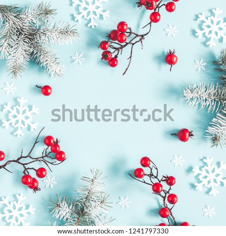 Christmas or winter composition. Frame made of snowflakes, fir tree branches and red berries on pastel blue background. Christmas, winter, new year concept. Flat lay, top view, copy space, square #1241797330