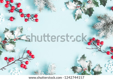 Christmas or winter composition. Frame made of snowflakes, fir tree branches and red berries on pastel blue background. Christmas, winter, new year concept. Flat lay, top view, copy space #1242744157