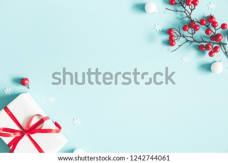 Christmas or winter composition. Gift, snowflakes, white balls and red berries on pastel blue background. Christmas, winter, new year concept. Flat lay, top view, copy space #1242744061