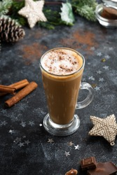 Christmas or winter hot chocolate drink. Tall glass up of fresh coffee latte with whipped cream, isolated dark background