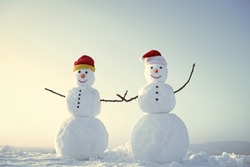 Christmas or xmas decoration. Snowman couple outdoor. Happy holiday and celebration. New year snowmen from snow in santa hat. Santa claus hat in winter.