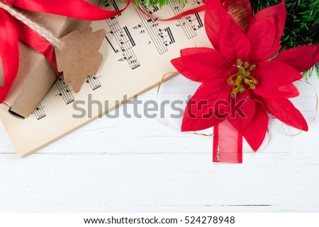 Christmas ornament and music sheet on white natural wooden table. Red ribbon bow. Poinsettia. Copy space at the bottom. Gift or present with label and twine.