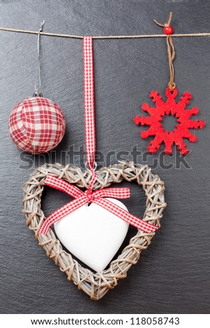 Christmas ornament: christmas ball, red snowflake and a wooden heart with a slate stone as background