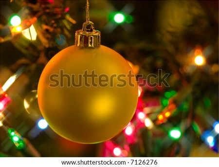 Christmas ornament hanging in Christmas tree against background of colorful lights - stock photo