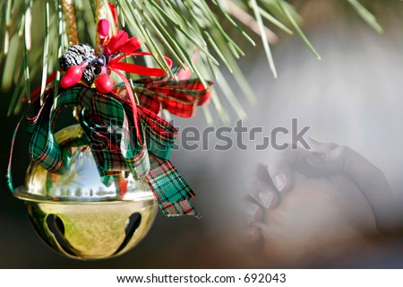 Christmas ornament in a pine tree with blended image of praying hands - represents faith and spirituality in the Christmas/Holiday season. - stock photo