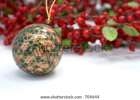 Christmas ornament laying beside a red holly wreath