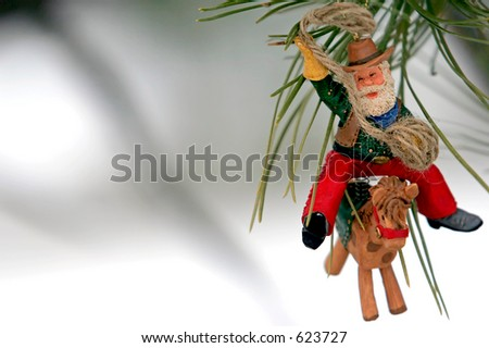 Christmas Ornament on pine tree in snow (Cowboy Santa)