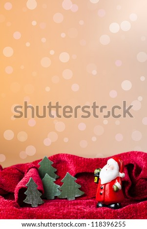 Christmas ornament: Santa Claus toy and little trees with a background of defocused lights