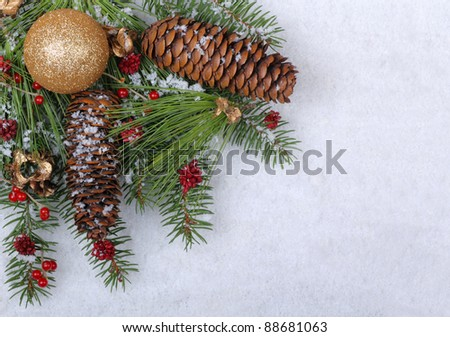 Christmas ornament with evergreen branches and pine cones on a white snowy background