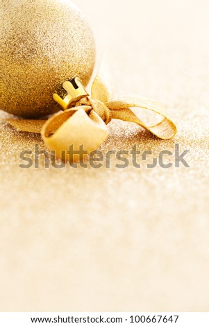 christmas ornament with ribbon on gold with copy space