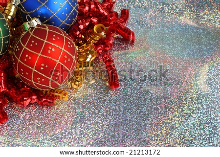 Christmas ornaments and curled ribbon on sparkling silver background with lots of copy space