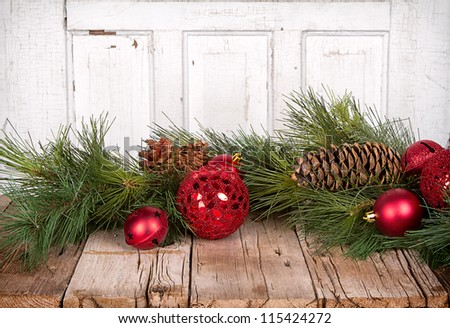 Christmas ornaments and pine branches on wooden background
