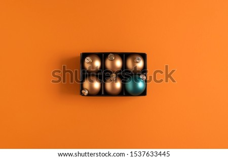Christmas ornaments context with gold Xmas balls and just one blue bauble in a black box on an orange background. Above view of Christmas balls.