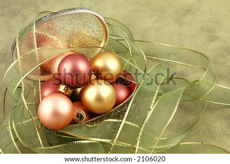 Christmas ornaments in a silver gift box surrounded by ribbon