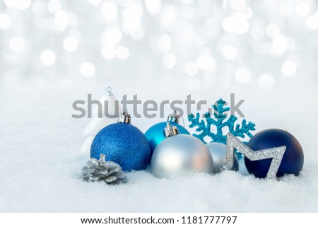 Christmas ornaments lying in the snow on a glade.