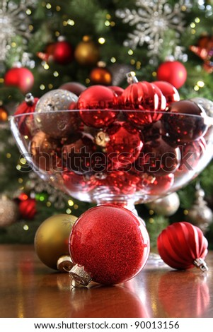 Christmas ornaments on table in front of holiday tree