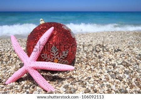 Christmas ornaments on the beach - stock photo