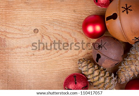 Christmas ornaments pine cones and rusty bells on a brown wood panel