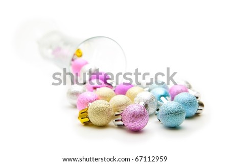 Christmas ornaments spilling out from a champagne glass. Isolated on white. Concept image for holiday season events and partys.