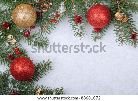 Christmas ornaments with evergreen branches on a white snowy background